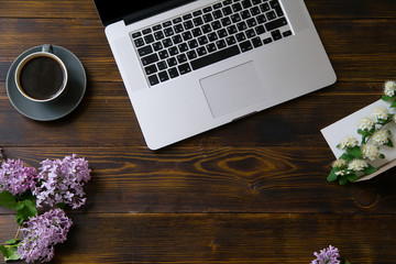 Flatlay with laptop and flowers on ol vintage wooden table
