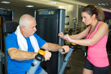 senior working out with a personal trainer standing beside him