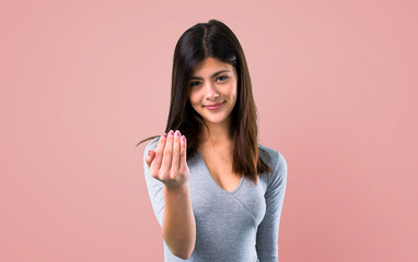 Teenager girl presenting and inviting to come on pink background