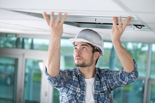 man in builder uniform hand up installing suspended ceiling