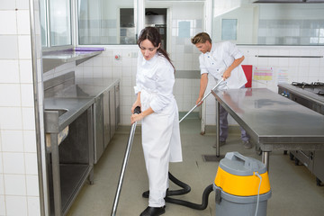 Workers cleaning kitchen floor