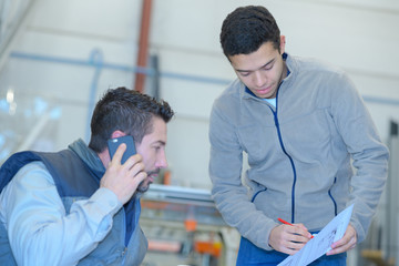 businessman using mobile phone with worker looking paper planes