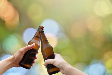 Hands holding two beer bottle and happy enjoying harvest time together to clinking glasses at outdoor party on beautiful bokeh light background.Celebration drinking beer in pub,bar.