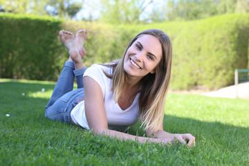 Hübsche blonde Frau liegt barfuß auf einem Rasen und lacht