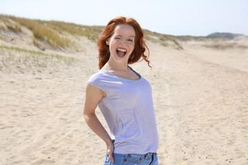 Hübsche rothaarige Frau steht lachend an einem Strand und zwinkert mit einem Auge