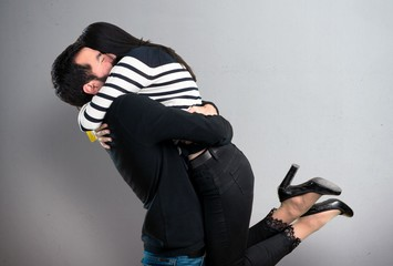 Young couple hugging on grey background