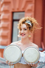 red-haired girl covers her chest with drums