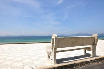 Banco con vistas a mar  y a las Islas Cíes con cielo azul con nubes