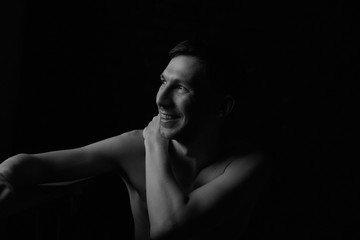 Black and white noir profile portrait of thoughtful handsome Caucasian topless male, tenderly touching his body, enjoying shape and fit, dreaming and resting in darkness. Fashion and beauty concept.