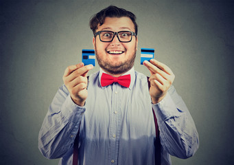 excited debt free business man in glasses holding a credit card cut in two pieces