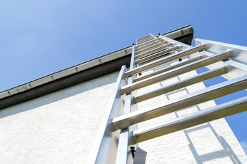 three section aluminum ladder leaning against house