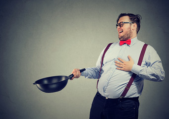 Excited professional man chef posing with frying pan.