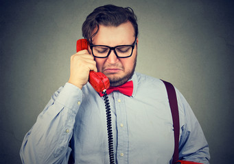 heartbroken sad man talking on telephone and looking unhappy feeling devastated
