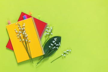 Lily of the valley and red and yellow notebooks