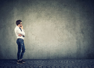 Pensive man looking at empty wall