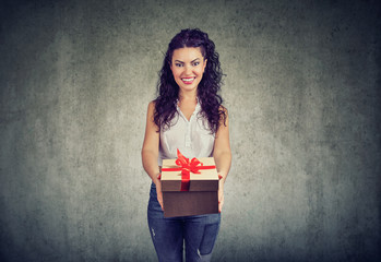 Pretty girl giving gift with red bow