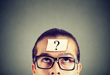 thinking man in glasses with question mark looking up