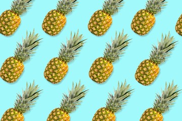 Colorful fruit pattern, Pineapples on a pastel blue background. Top view.