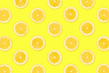Colorful fruit pattern, Lemon slices on a bright yellow background. Top view.