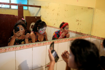 Clowns prepare themselves to take part in a parade during Peru's Clown Day celebrations in Lima