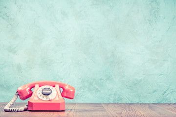 Retro classic outdated pink rotary telephone on wooden desk front textured aquamarine concrete wall background. Vintage instagram old style
