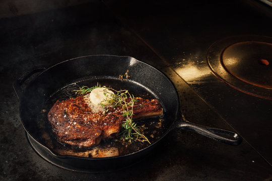 Cooking steak in a cast iron pan.