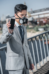 asian businessman in gas mask showing smartphone on bridge, air pollution concept