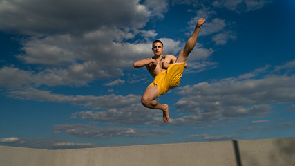 Tricking on street. Martial arts. Man does high kick in jump barefoot. Shooted from bottom foreshortening against sky.
