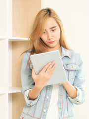 Young woman using tablet computer in living room.