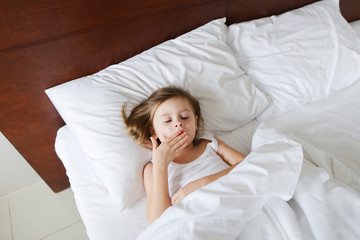 Little cute girl lying in bed and yawning in morning. Concept of chidhood and waking up.