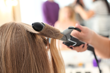 Professional hairdresser working with client in salon. Apprenticeship concept
