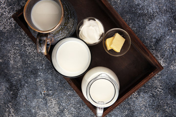milk products - tasty healthy dairy products on a table sour cream in a bowl, cream and milk jar