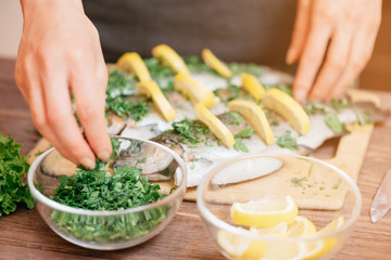 Female hands preparing fish with lemons and greenery.
