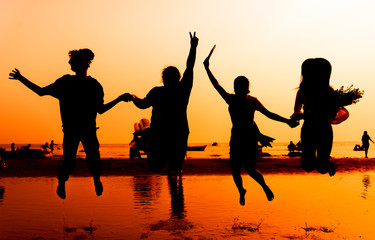silhouette Group of friend Happiness relaxing on the beach with sunset background.