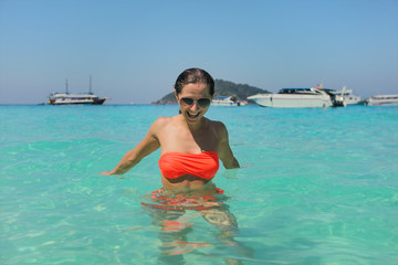 Young woman in orange red bikini and sunglasses, in crystal clear water smiling. Similan Islands, Thailand
