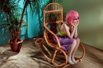 beautiful stylish girl in pink wig sitting in rocking chair and looking away