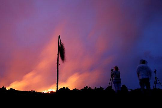 Spectators take pictures of the Kilauea lava flow in the Leilani Estates near Pahoa, Hawaii