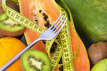 tropical fruits and fork with tape measure. Diet and health concept