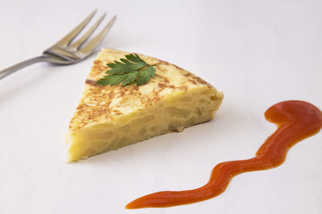 portion of spanish potato and onion tortilla with tomato sauce