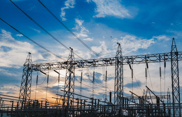 Sunset behind substation towers with blue sky