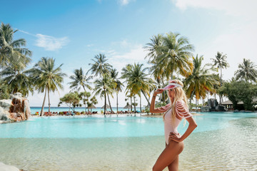 sexy woman with blond hair in elegant beach clothes relaxing in Maldive island