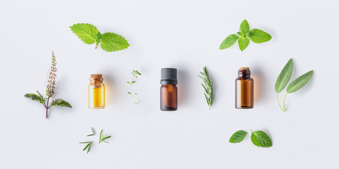 Door stickers Condiments Bottle of essential oil with fresh herbal sage, rosemary, oregano, thyme, lemon balm spearmint and peppermint setup with flat lay on white background