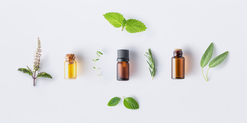 Tuinposter Aromatische Bottle of essential oil with fresh herbal sage, rosemary, oregano, thyme, lemon balm spearmint and peppermint setup with flat lay on white background