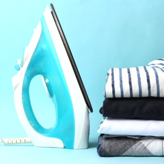 A stack of clothes and an iron on a colored background. minimalism, ironing clothes.