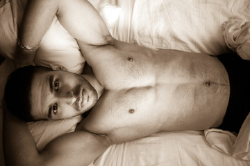 Semi naked handsome arab man in bed with defined body looks at camera