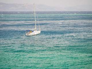 Single yacht in the open blue sea against the backdrop of the mountains