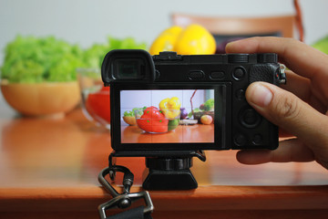 Photographer taking photo of fresh fruits and vegetables on camera display while shooting in kitchen table