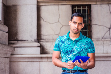 Young Hispanic American college student wearing green patterned Polo shirt, sitting on vintage street on campus in New York, holding blue tablet computer, reading, thinking. Modern City Life.