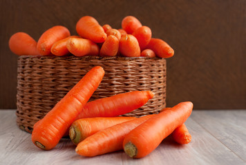 Harvest carrots in a wicker basket. A lot of carrots in a large wicker basket on a wooden background. Orange vegetables.