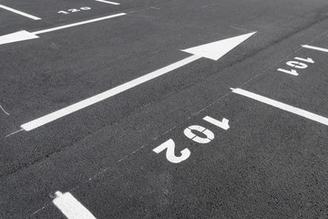 Fresh painted parking places, gray new asphalt, white arrows and numbers